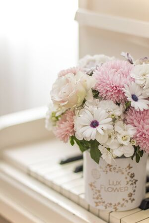 Bouquet of flowers in a beautiful box on a white piano. Bouquet of asters, hydrangeas and daisies. Bridal bouquet. Zdjęcie Seryjne - 132051824