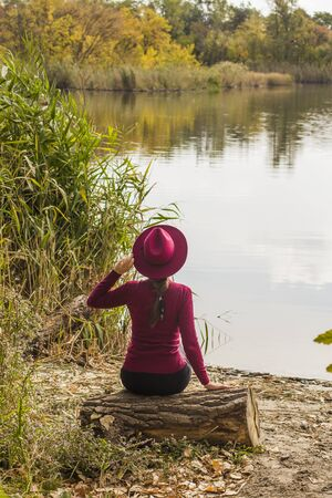 Beautiful girl on the lake. Beautiful girl in a hat. Girl in a burgundy hat and a burgundy sweater. Autumn photo. View from the back. Teenager, a woman is sitting on a log. Banco de Imagens