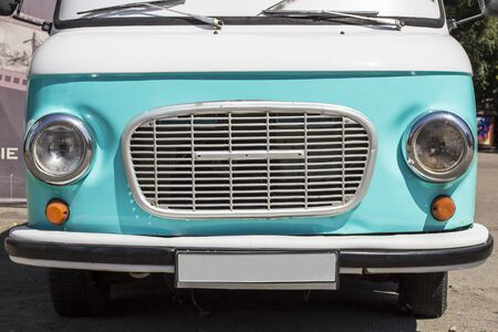 Front of a retro car. Turquoise exclusive car. Bumper, grille, headlights. The concept of travel, delivery. Minibus front Stock Photo