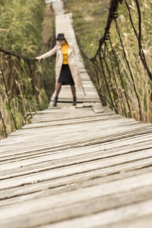 Beautiful girl on a suspension bridge. Woman in a black hat and a beige trench coat. Pretty girl on the suspension bridge. Fashionable autumn woman. Girl in black leather boots. 写真素材