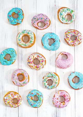 Colorful Donuts turquoise and pink, pattern. Donuts Set on White Background. Doughnuts with multi colored glaze. Doughnuts are traditional sweet pastries. Set of various colorful donuts.