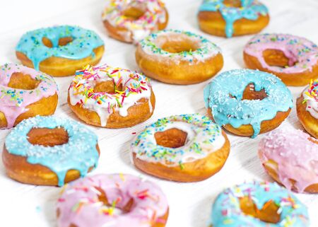 Colorful Donuts turquoise and pink, pattern. Donuts Set on White Background. Doughnuts with multi colored glaze. Doughnuts are traditional sweet pastries. Set of various colorful donuts. Stock Photo