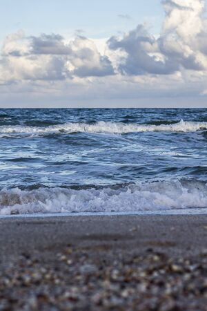 Sea waves, sandy beach and clouds Stok Fotoğraf