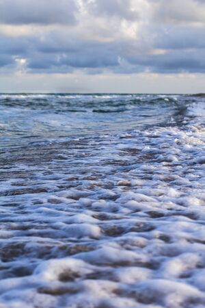 Sea waves, sandy beach and clouds Archivio Fotografico