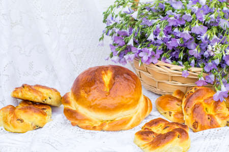Delicious pastries (bread and rolls with raisins) and bouquet linen in wicker basket Archivio Fotografico