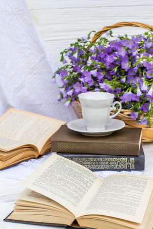 cup coffee (tea), books and bouquet flax in wicker basket