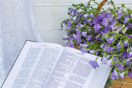 Open Bible and bouquet flax in wicker basket Stok Fotoğraf