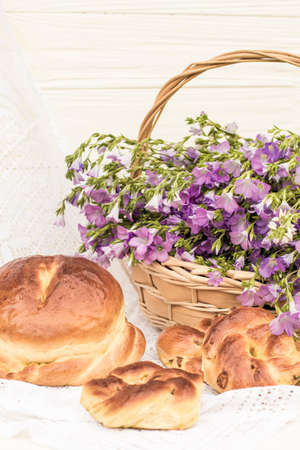 Delicious pastries (bread and rolls with raisins) and bouquet linen in wicker basket. Retro style, vintage Archivio Fotografico