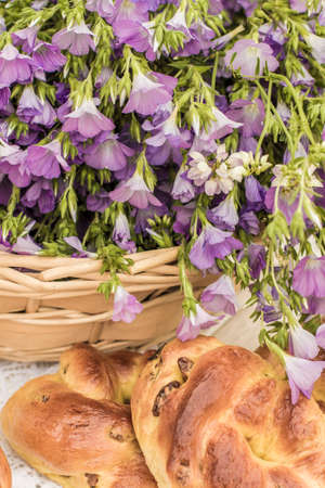 Delicious pastries (rolls with raisins) and bouquet linen in wicker basket. Retro style, vintage