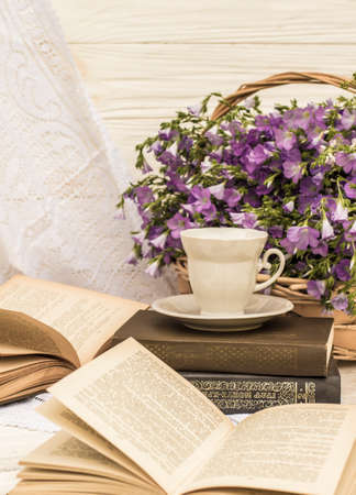 cup coffee (tea), books and bouquet flax in wicker basket. Retro style, vintage Stok Fotoğraf