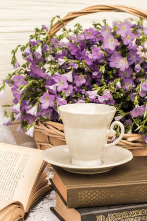 cup coffee (tea), books and bouquet flax in wicker basket. Retro style, vintage Archivio Fotografico