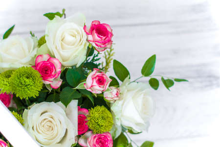 Wooden box with white and pink roses and chrysanthemums on white wooden board. Decoration of home. Flowers boxes. Wedding decoration