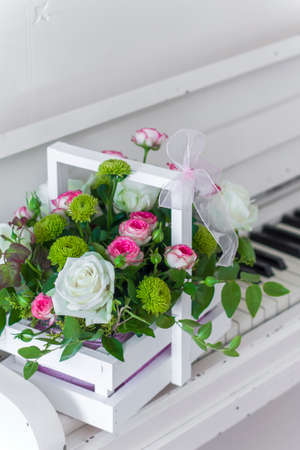 White wooden box with bouquet white and pink roses and chrysanthemums on white piano. Decoration of home. Flowers boxes. Wedding decoration