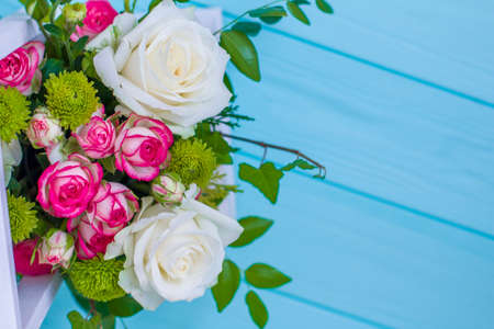 Wooden box with white and pink roses and chrysanthemums on turquoise wooden board. Decoration of home. Flowers boxes. Wedding decoration