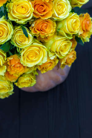 bouquet of yellow roses and pumpkin on black wooden board. Beautiful yellow roses. Autumn decor