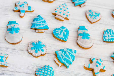 Homemade gingerbread cookies pattern. Christmas gingerbread. Gingerbread man, snowman, heart, star, Christmas tree, snowflake. Decorated sweets for Christmas and New Year on wooden white background 版權商用圖片