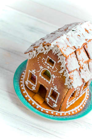 Gingerbread house on white wooden background