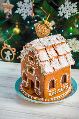Christmas Gingerbread House with glaze On Wooden Table On Background Of Christmas Tree With Burning Garlands Close Up. Festive mood. Christmas morning. Gingerbread house
