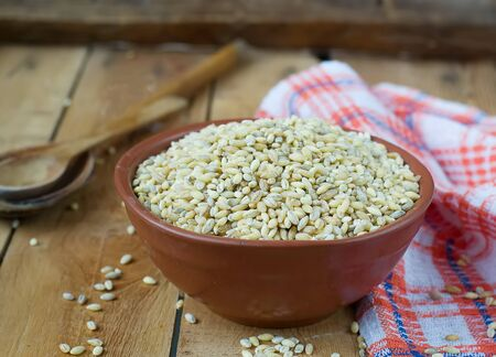 pearl barley: Pearl barley in a ceramic bowl on a wooden background