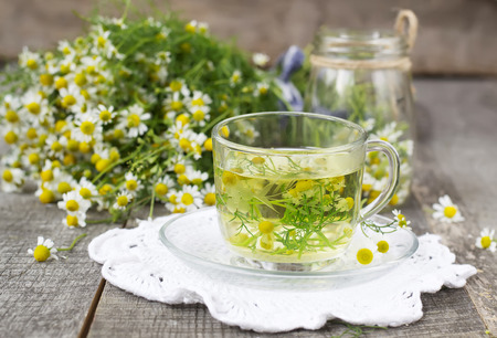 sedative: Chamomile tea in a glass cup on a wooden background Stock Photo
