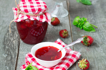 confiture: Confiture with strawberries and basil on a wooden background