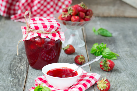 preserve: Confiture with strawberries and basil on a wooden background
