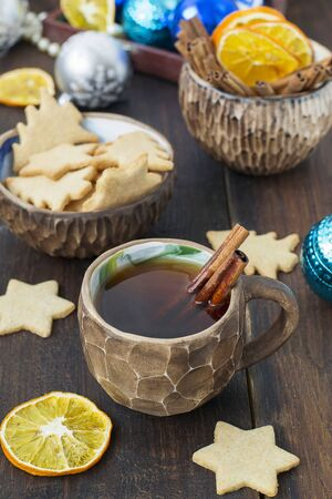 Tea with spices in a clay cup of ginger biscuits and Christmas decorations.