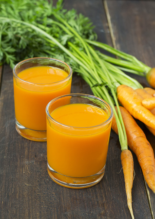 carrot juice in a glass on a wooden background