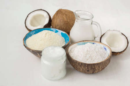 Set of coconut products, butter, milk, flour, chips, on a white background