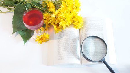 Still Life of yellow flowers, books and A red wine isolated on white background