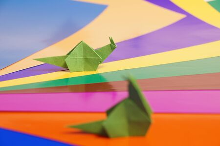 Paper origami snail isolated on a colorful background