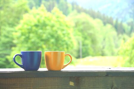 A beautiful cup with hot tea stands in front of a beautiful scenery Stock Photo