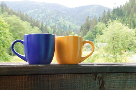 daybreak: A beautiful cup with hot tea stands in front of a beautiful scenery Stock Photo
