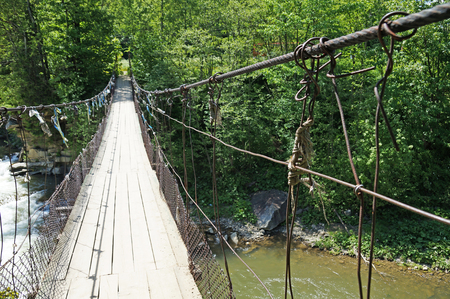 Suspension bridge across the mountain river swaying from the wind. Bridge over the river