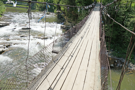 swaying: Suspension bridge across the mountain river swaying from the wind. Bridge over the river