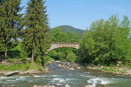 carpathians: A bridge over a mountain river in the Ukrainian Carpathians. Bridge over the river Stock Photo