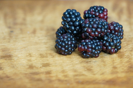 Ripe and juicy blackberries isolated on a wooden background.