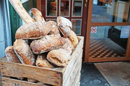 Freshly baked, fragrant, soft and spiky bread. A lot of bread is sold in the store. Belgian bread. Many different breads are stored in a wooden box. Stock Photo
