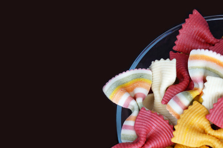 Multicolored pasta. Beautiful pasta in the form of a butterfly. Original italian pasta isolated on a black background. Figured pasta on a black background.