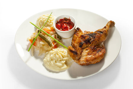 Grilled chicken thigh with sauce and mashed potatoes isolated on white photo
