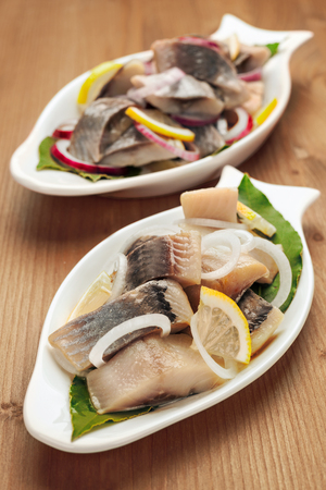 Seafood appetizer herring fish fillet with vegetables, white plates in the form of fish photo