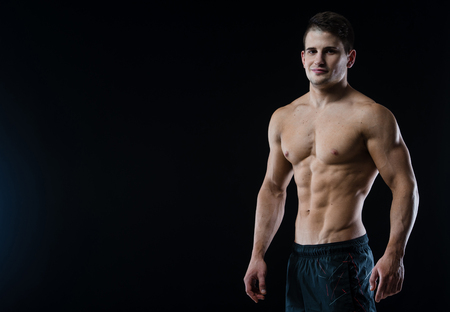 six pack: Man showing his six pack abs on black background