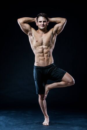 joga: Young strong athlete is making yoga on black background