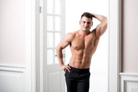 bare waist: Athlete man standing in the doorway home interior