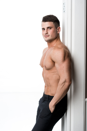 laying abs exercise: Athlete man standing in the doorway home interior