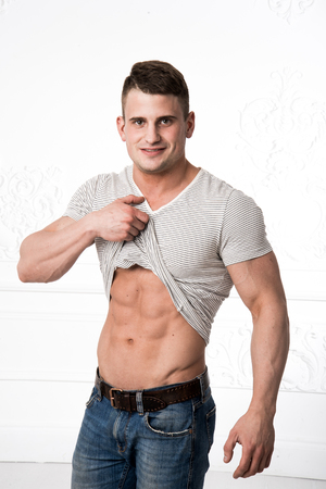 retouched: Torso of strong guy in jeans against white background