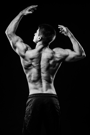 latissimus: Young strong athlete on dark background isolated Stock Photo