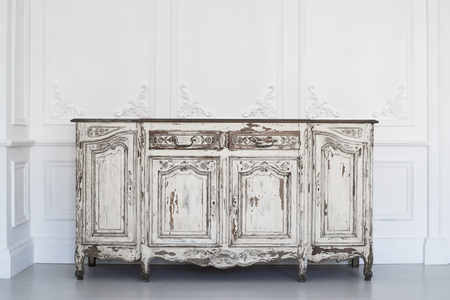 Antique white chest of drawers with fretwork wall on backround Archivio Fotografico