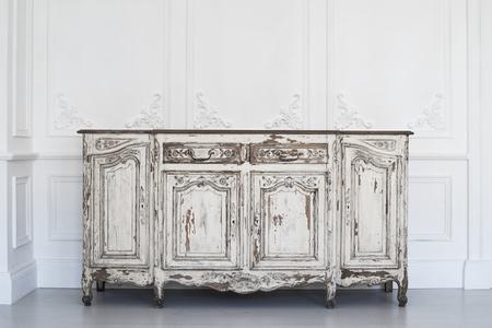 arredamento classico: Antico petto bianco di cassetti con muro di traforo su backround Archivio Fotografico
