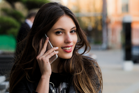 Closeup young happy beautiful smiling woman girl lady talking on mobile cell phone isolated cityscape outdoor street background.